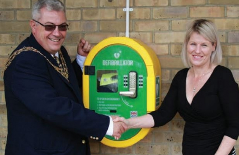 The Mayor unveils the defibrillator with Carol Martens, centre manager.